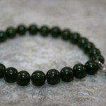Nephrite jade stacking stretch bracelet with antiqued sterling silver pinecone charm