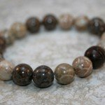 Fossil coral and brown snowflake jasper stacking stretch bracelet with carved rosewood focal bead