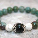 Green aventurine stacking stretch bracelet with white howlite and buri root flanked by sterling silver bead caps