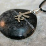 Wire wrapped Picasso marble teardrop pendant with antiqued sterling silver Chinese friendship symbol on black cotton cord