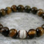 Tigereye stacking stretch bracelet with a white howlite focal bead flanked by antiqued copper bead caps