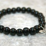 Obsidian stacking stretch bracelet with a sterling silver open butterfly charm