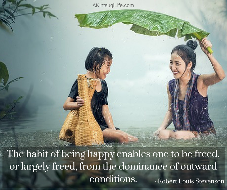 woman and girl smiling in river during heavy rain while holding a large leaf overhead
