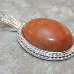 Sunstone cabochon in a silver plated bezel on silver plated snake chain