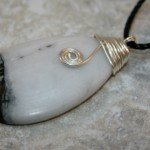 Green earth jasper stone teardrop pendant with silver plated wire wrapping and spiral on black cotton cord