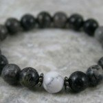 Black and grey marble stacking stretch bracelet with a white howlite focal bead and blackened metal spacers