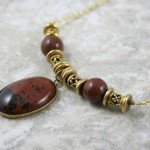 Mahogany obsidian cabochon in a brass bezel cup with brass and mahogany obsidian accents on brass chain