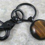 Tiger eye stone key chain in a black bezel setting and swivel lobster claw
